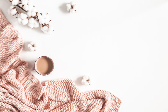 Cup of coffee, pink blanket, cotton flowers on white background. Flat lay, top view, copy space