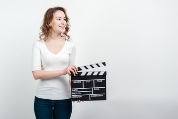 Attractive woman holding a clapboard isolated over white background