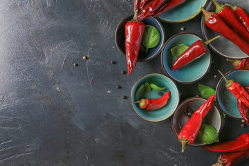 Canvas Prints Hot chili peppers chili peppers with basil and peppercorns in bowls on a rustic surface,