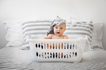 Funny baby sitting in a laundry basket with clothes on top of head