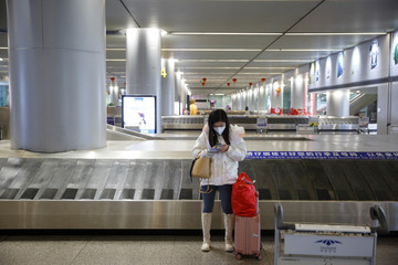 A woman wearing a face mask stands in the empty luggage collection hall at the airport in Changsha