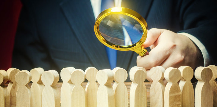 Businessman is studying a crowd of people with a magnifying glass. Hr search candidates for work, staff recruiting. Society, demographic. Market and customers research. Citizens electorate. Sociology
