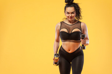 Size plus woman sporty fit woman in black sportswear, athlete with dumbbells makes fitness exercising on yellow background. Motivation for fat people.