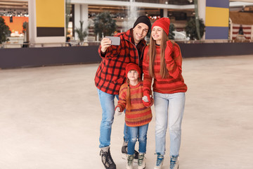 Happy family taking selfie on skating rink