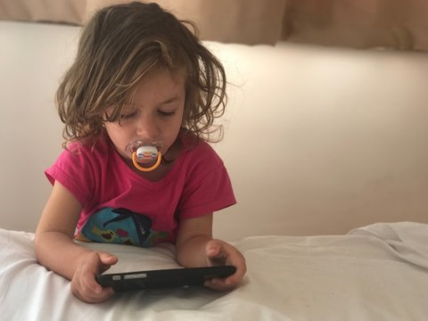 Girl With Pacifier In Mouth While Using Phone On Bed