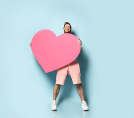 Young handsome man in white polo shirt hold pink heart shape toy present gift happy valentines day...