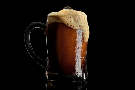 Cold beer mug with black stout covered with drops and froth studio shot on black background.