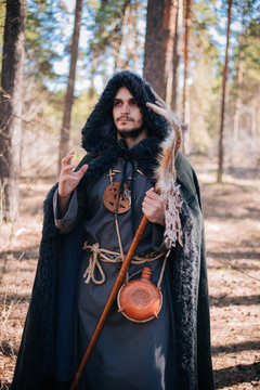 A man with a beard and a mustache in a robe and coat with a staff in his hand. A magician, a shaman conjures in the forest. Fantasy image