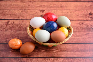 Raw eggs and color easter eggs on wooden table, in basket.