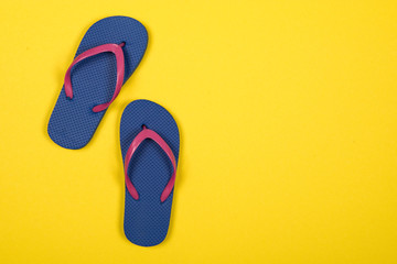 Pink and blue flip flops on a yellow background with copy space
