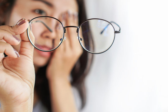 Asian woman hand holding eyeglasses having problem with eye pain, blur vision
