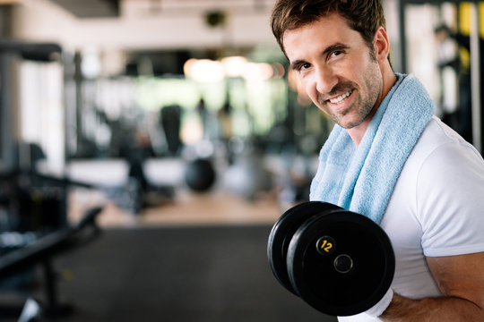 Determined young male working out in gym