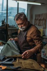 Fototapeta attentive, senior cobbler looking at pieces of genuine leather in workshop
