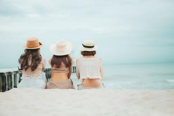three woman wearing straw hat  sitting on vacation sea beach