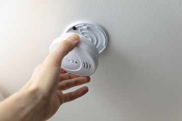 hand installing smoke detector on the room ceiling