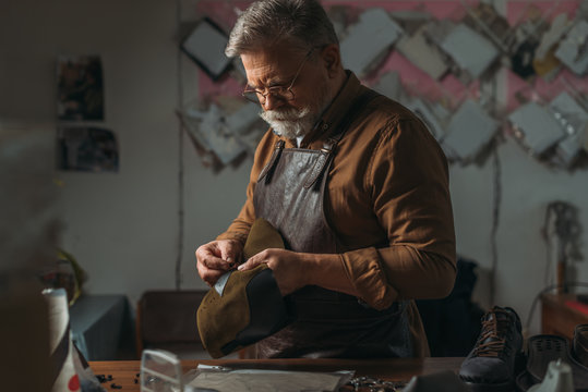 selective focus of senior cobbler holding piece of genuine leather in workshop