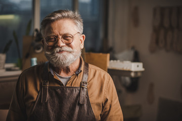 happy, senior shoemaker in glasses smiling at camera while standing in workshop