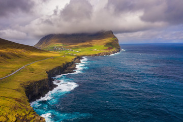 Wall Mural - Aerial view of a road going along the coast to a village on Faroe Islands