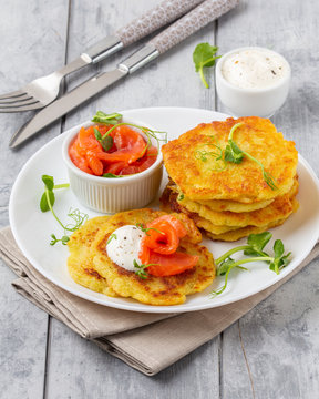 Fried potato pancakes with salmon and sour cream, fritter, roesti, golden crispy crust. Traditional delicious food