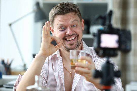 Drunk male director holds a glass with whiskey in hand and greets his subservient portrait. Work of dream concept