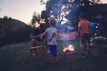 Father with children making a camping fire in the backyard.