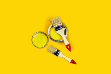 Renovation picture. Yellow background with one paint can and two brushes. Flat lay, top view, copy space.