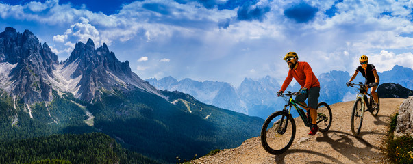 Cycling woman and man riding on bikes in Dolomites mountains andscape. Couple cycling MTB enduro...