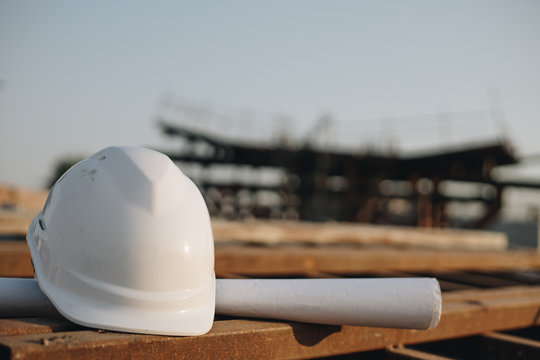 white helmet for security and blueprint on construction site
