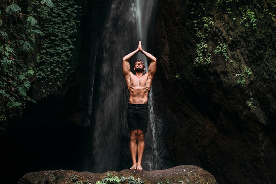 A man of athletic build does yoga. Healthy lifestyle. The concentration of the body. A man does yoga in nature. A man does yoga in Bali. A man meditates in nature. Meditation at the waterfall
