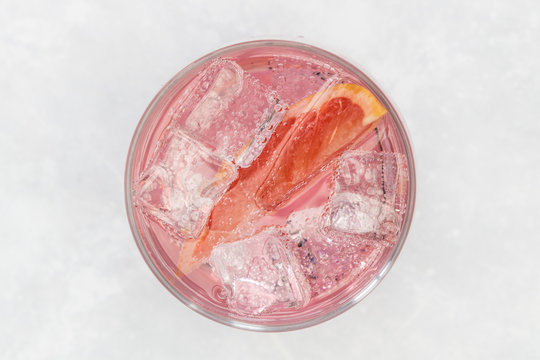 Pink gin tonic vodka soda fruit grapefruit cocktail drink in glass with ice, top view on white background