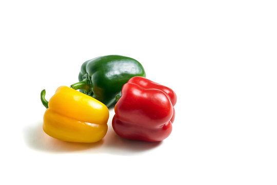 Red, green, and yellow bell peppers isolated on white background. Three sweet peppers in different colors, vegetable ingredient, healthy food