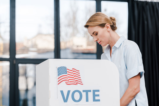 side view of attractive woman voting near stand with vote lettering and american flag