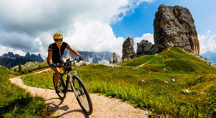 Tourist cycling in Cortina d'Ampezzo, stunning Cinque Torri and Tofana in background. Woman and man riding MTB trail. South Tyrol province of Italy, Dolomites.