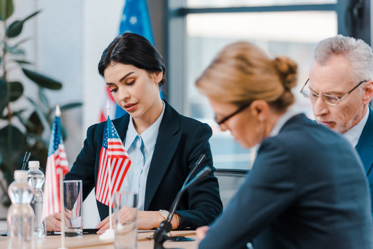 selective focus of attractive businesswoman near diplomats and flags of america