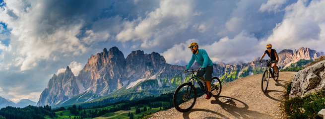 Cycling woman and man riding on bikes in Dolomites mountains andscape. Couple cycling MTB enduro trail track. Outdoor sport activity. Wall mural