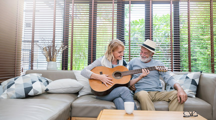Portrait of caucasian senior grand parent couple enjoy practising guitar. Married mature man woman playing on music instrument. Love together valentines' day of old people. Lifestyle holiday banner