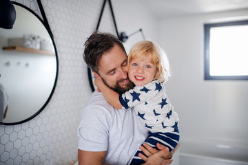 Wall Mural - Mature father with small son indoors in bathroom, hugging.