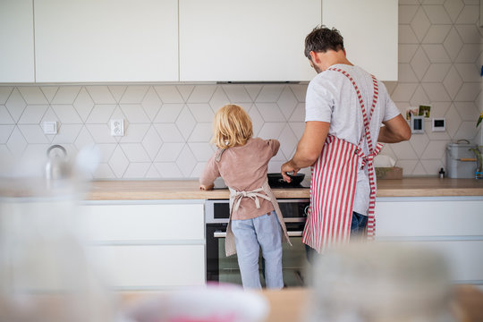 A rear view of small boy with father indoors in kitchen making pancakes.