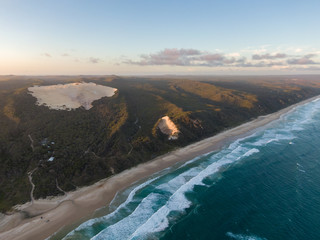 "High angle aerial drone view of famous Seventy Five Mile Beach near Dundubara Creek on Fraser Island, Queensland, Australia, shortly before sunset. ""Sand blow"" dunes in the background."