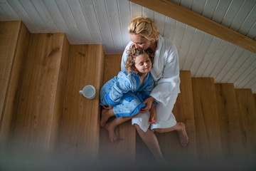 Wall Mural - Top view of small girl with mother indoors at home, sitting on stairs in the morning.