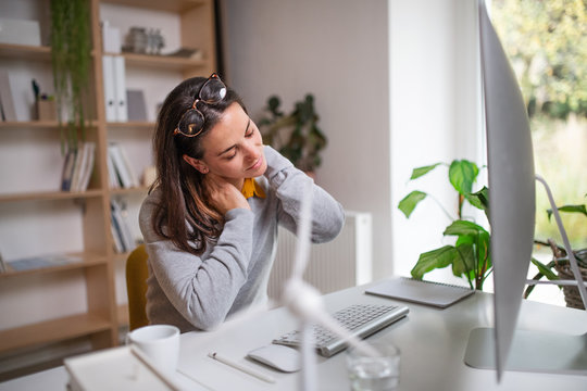 Businesswoman at the desk indoors in office, feeling pain in neck.