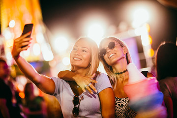 two girls taking selfie at the music festival
