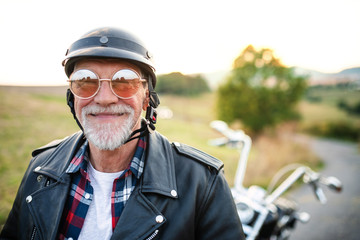 A cheerful senior man traveller with motorbike in countryside, headshot. Wall mural