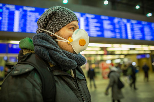 Man wearing a respirator mask device for health protection at an airport or railway train station in a crowd of people while travelling. Epidemic corona virus infection, flu sickness travel concept