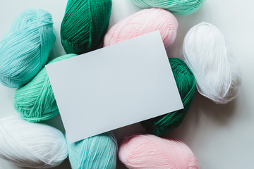 white paper sheet on acrylic soft pastel colored wool yarn thread skeins heap on white background, top view flat lay horizontal stock photo image mockup with copy space for text