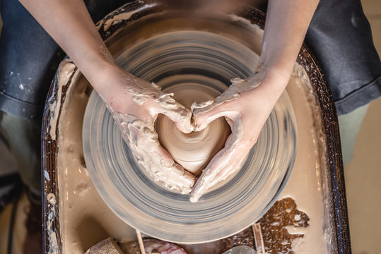 Potter working with clay on a Potter's wheel. Women's hands show a heart sign. Concept of love for pottery art