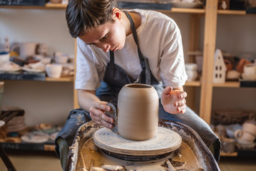 Potter working on a Potter's wheel making a vase. Master processing the formed jug giving it the correct shape