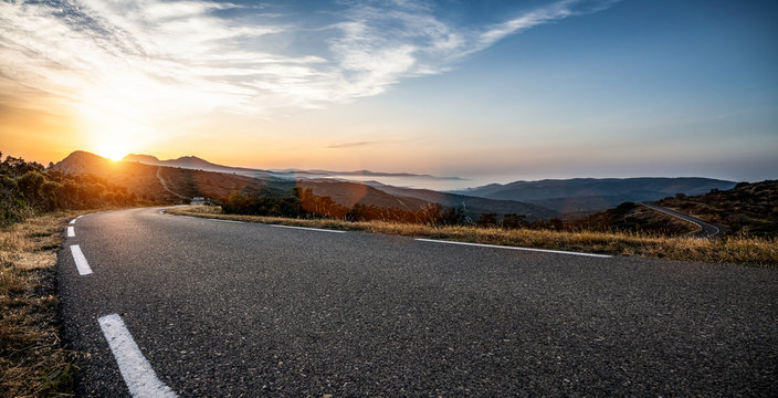 Empty long mountain road to the horizon on a sunny summer day at bright sunset