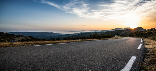 Empty long mountain road to the horizon on a sunny summer day at bright sunset Fototapete
