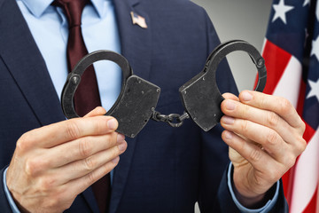 Male in suit holding metal handcuffs with USA flag on background - close up studio shot